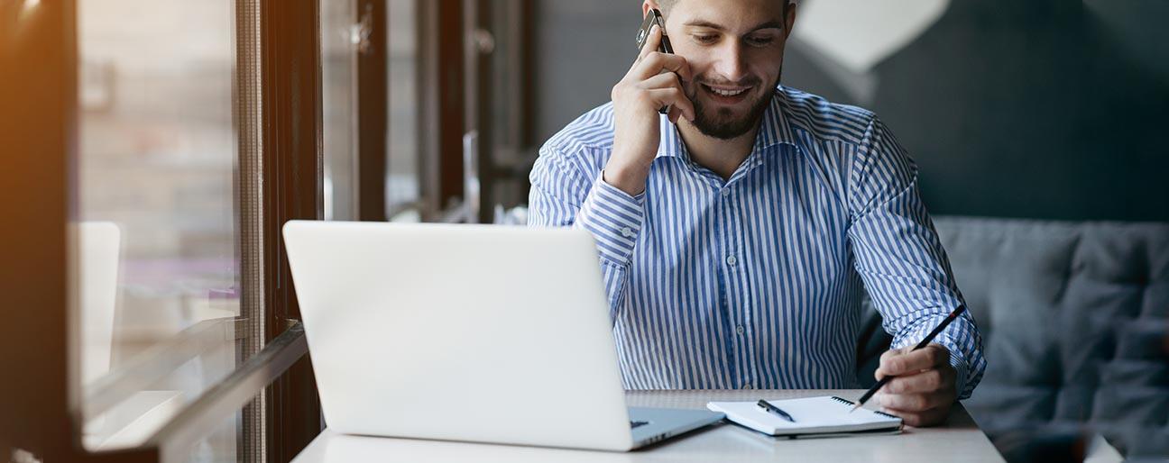 Man som pratar i telefon framför en dator och papper & penna